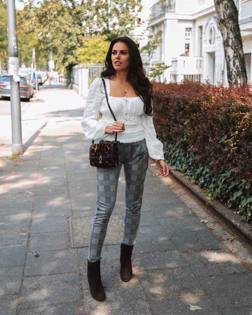 Rebecca Garcia mit animal print Tasche mit weißer Bluse und Glencheck Hose