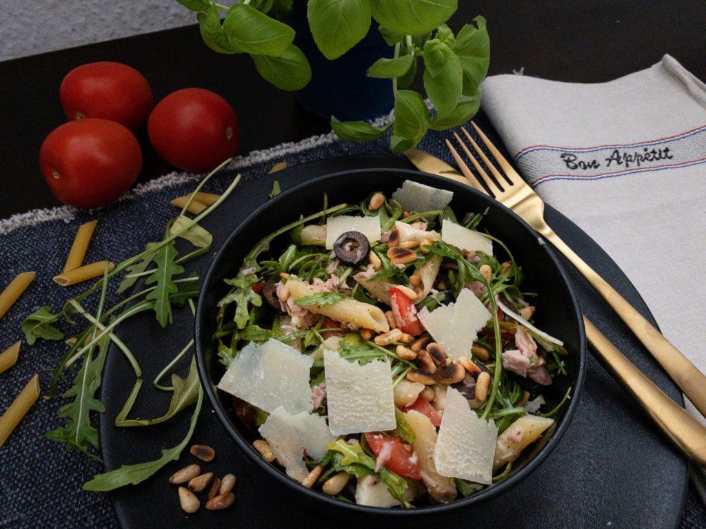 mediterraner Nudelsalat in einer schwarzen Bowl und goldenem Besteck